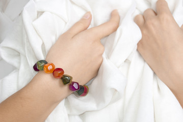 Girl's hands with multicolor bracelet on a white cloth