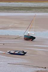 Marooned sail boat and dinghy at low tide