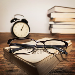 Glasses on the books and clock
