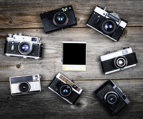 Group of vintage cameras around single blank photograph