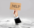 Hand of  businessman holding help message on paperwork desk