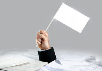 Hand of  businessman holding white flag on paperwork full desk