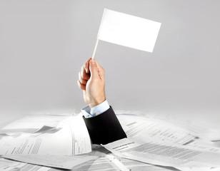 Hand of  businessman holding white flag on paperwork desk