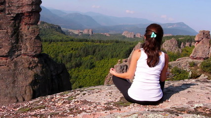 Woman doing yoga exercises on Belogradchik rocks