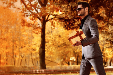 Handsome man in suit with a girt. Autumn.