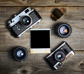Vintage cameras with lenses and blank old photograph on wooden b