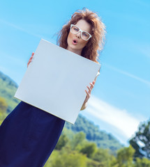 Expressive funny woman holding white board
