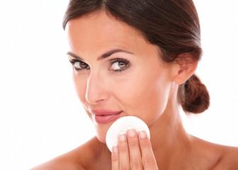 Latin woman applying moisturizer on her face