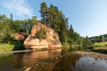 river with reflections in water and sandstone cliffs