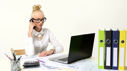 Beautiful businesswoman using laptop and a phone