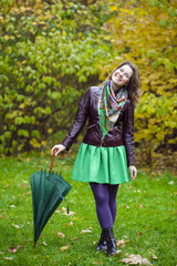 Woman with green umbrella smiling as raining