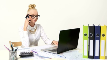Happy businesswoman using laptop and a phone