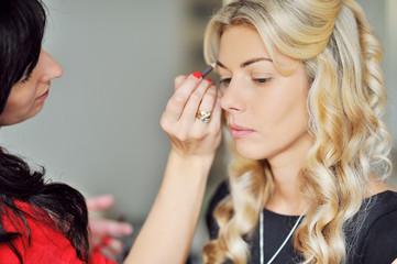 Makeup artist applying makeup on models eyebrows