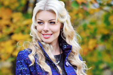 Beautiful elegant smiling woman standing in a park in autumn