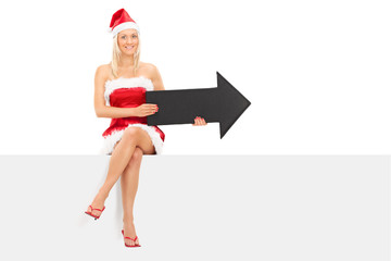 Girl in Santa costume holding an arrow seated on a panel