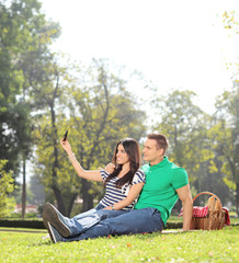Girl taking a selfie with her boyfriend in a park