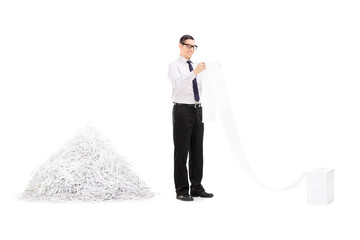 Man reading file in front of pile of shredded paper