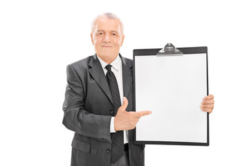 Mature businessman pointing on a clipboard
