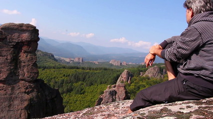 Man sitting on a rock and admiring beautiful Belogradchik valley