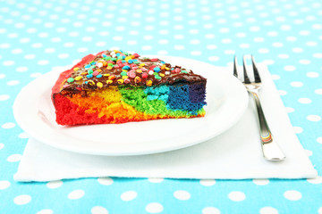 Delicious rainbow cake on plate, on tablecloth background