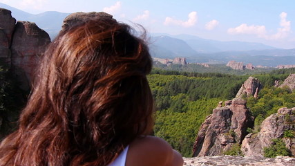 Woman sitting on a rock & admiring beautiful Belogradchik valley