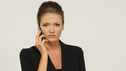 Portrait of a business woman talking the phone, isolated on