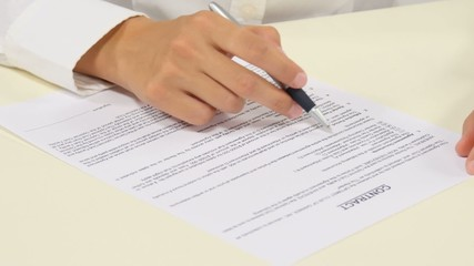 Business worker signing the contract to conclude a deal