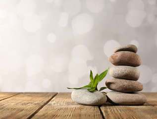 Spa stones and bamboo on wooden table on light background