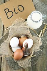 Eggs and fresh milk in glass jug with inscription BIO  ,
