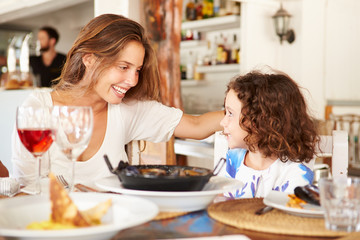 Mother And Daughter Enjoying Meal In Restaurant