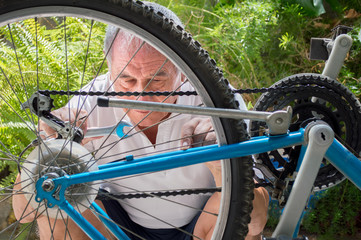 mature repairing a bicycle