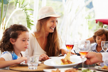 Mother With Children Enjoying Meal In Restaurant
