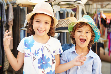 Children On Vacation Trying On Hats At Store