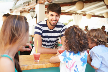 Man Making Children Fruit Smoothies In Restaurant