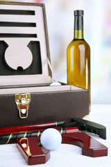 Golf set in suitcase with bottle of wine