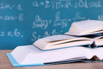 Books on wooden table on blackboard background