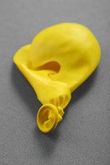 Popped yellow balloon on paper background
