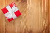Fototapety Red gift box over wooden background