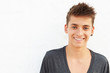 Portrait Of Hispanic Teenage Boy Leaning Against Wall