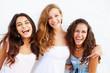 Leinwandbild Motiv Portrait Of Three Teenage Girls Leaning Against Wall