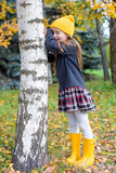 Little girl playing hide and seek in autumn forest outdoors poster