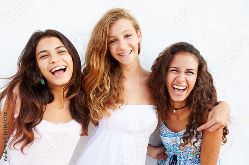 Portrait Of Three Teenage Girls Leaning Against Wall - 71673770