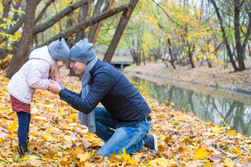 Young father have fun with cute daughter in autumn park