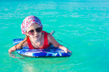 Little adorable girl on surfboard in the turquoise sea