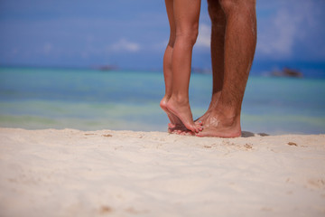 Little girl and her father feet at white sandy beach