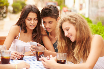 Group Of Teenage Friends Using Mobile Phone Sitting At Caf'