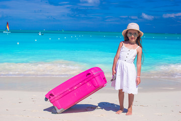 Little adorable girl with big luggage in hands on tropical beach