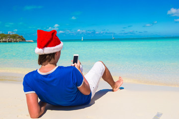 Young man in santa hat on tropical beach