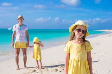 Adorable little girls and happy father on tropical white beach