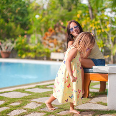Young mother and her little daughter have fun near swimming pool